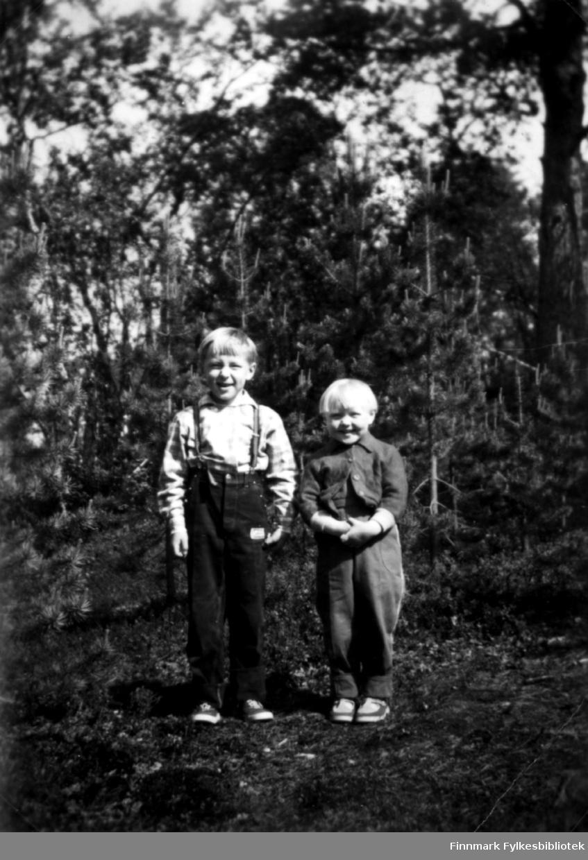 Fotografi av Trygve og Ingrid Stenbakk. På bildet står de ved, eller i en skog. Det er mange trær i bakgrunnen. Begge barna har 'pottefrisyrer'. Trygve er kledt i skjorte og bukser med seler. Ingrid har på seg bukse og jakke. Det ser ut som et sett