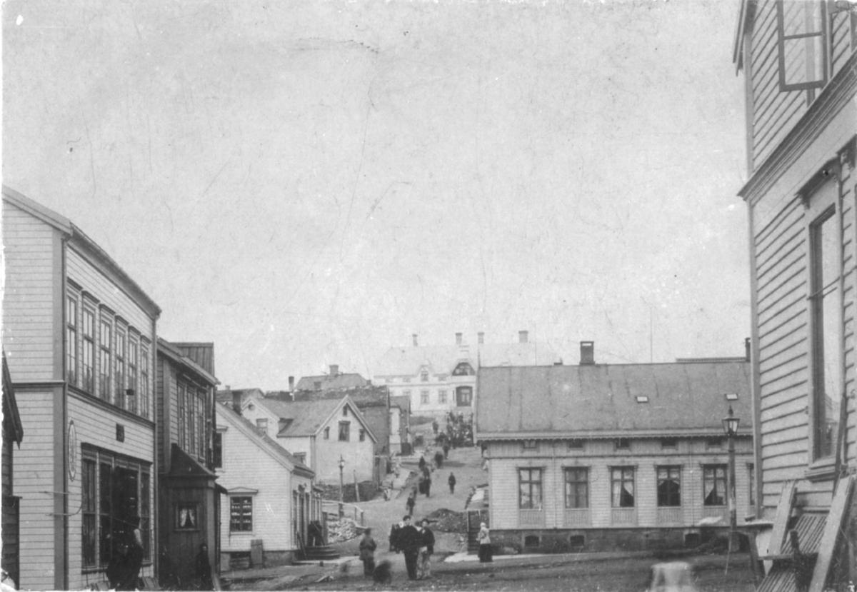 Tollbodgaten i Vadsø fotografert fra torget og oppover mot Amtmannsgården. Det er mennesker i gatene, og bildet viser boliger og forretninger langs gata