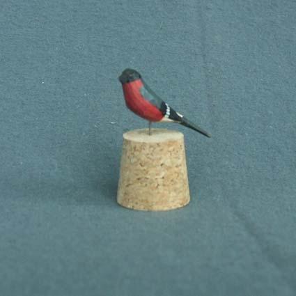 Liten täljd och målad fågel med metallnål fastsatt undertill.