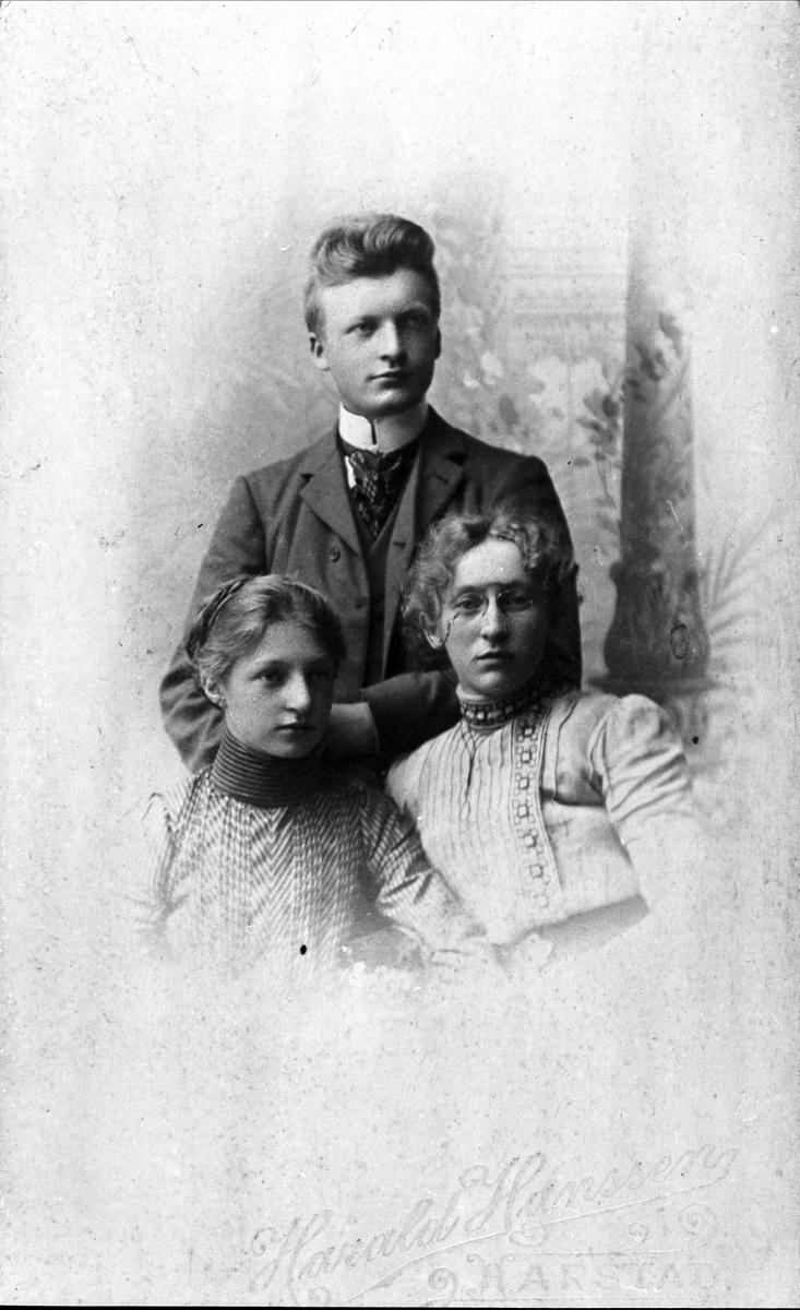 Studioportrett av to kvinner og en mann.