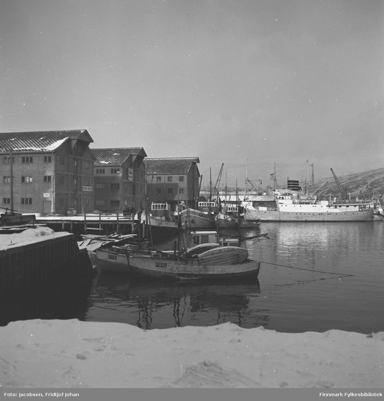 Hammerfest havn med noen fiskebåter ved kai. Den store båten til høyre i bildet er en FFR-båt, usikkert om det er M/S Ingøy eller Brynilden. De store byggene på kaia er Trygve Nissens forretning og lager. Lengst borte ligger Televerkets lager som i dag huser biblioteket.