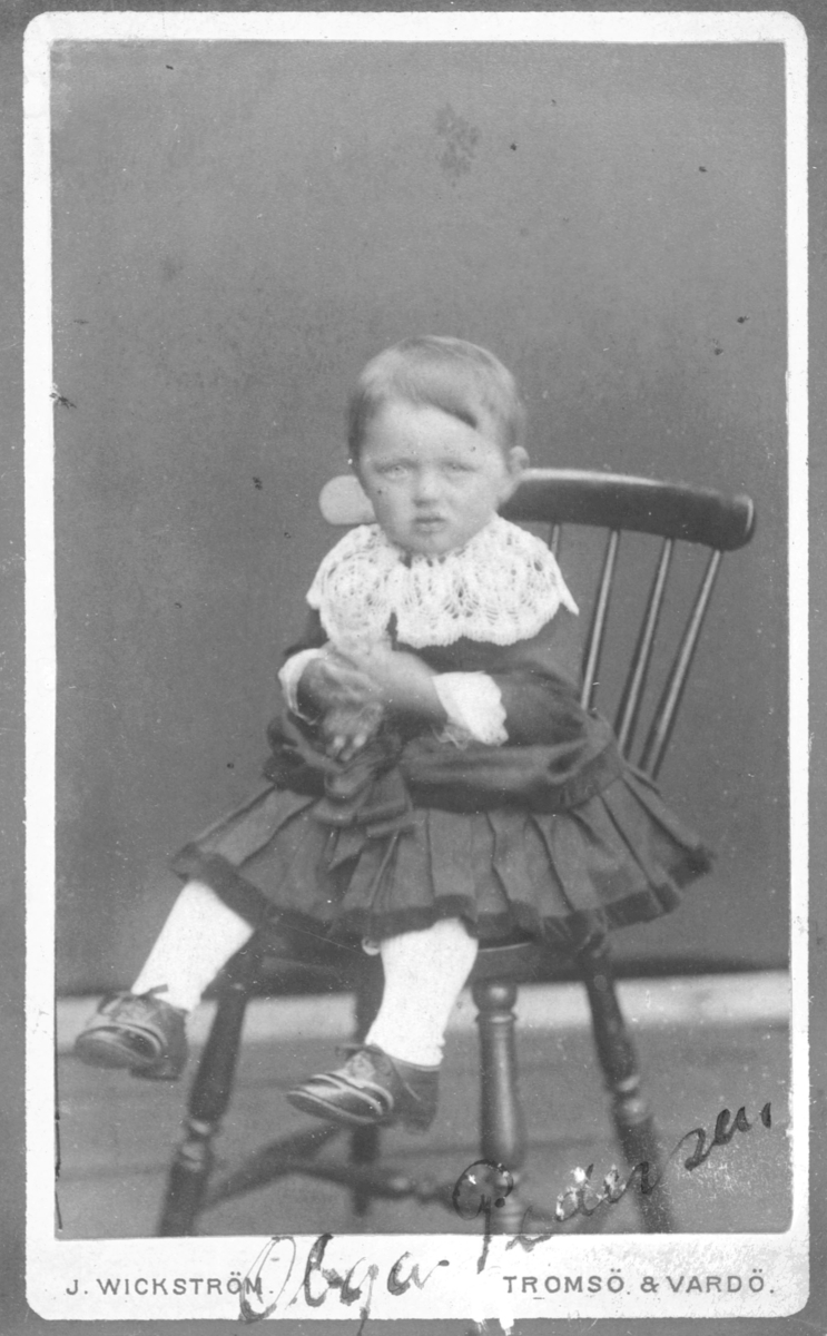 Portrett av en liten jente, Olga Marie Pedersen. På bildet er hun 3 år gammel og sitter i en pinnestol med en dukke på fanget. Visittkortportrettets bakside viser at bildet er tatt av J. Wickstrøm som hadde filial i Vardø og Tromsø og bildet er tatt i 1889. Dette er sannsynligvis Olga Marie Pedersen født 1885 i Vardø og senere kontordame i Vadsø. Hennes far var Vexel Pedersen og mor Nanna Evida Pedersen. Vexel Pdersen er registrert som Portner ved Politistasjonen og Kommunalt bud i Digitalarkivet. Nanna Evida Pedersen er registrert som Hustru og sydame. Det finnes flere bilder av Olga Marie i dette albumet, også som 17åring.  Bildet er bevegelses-uskarpt, noe som skyldes at det på denne tiden var ganske lange eksponeringstider og de fleste bilder ble tatt med dagslys fra et vindu som eneste lyskilde. Olga er kledt i en kjole med stor heklet blondekrage og mansjetter, hun har hvite strømper og snørede skinnsko på beina.