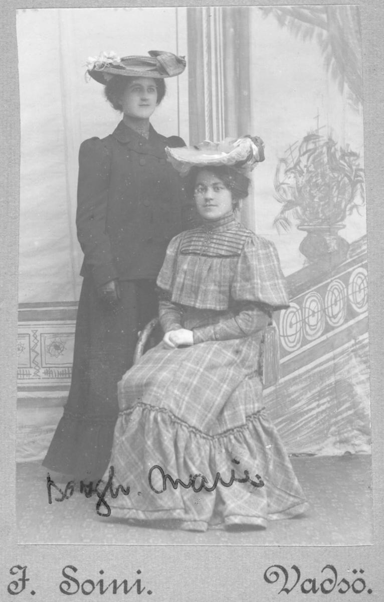 Gruppebilde av to unge kvinner. Kvinnen til høyre sitter på en stol ikledd en rutete, lang kjole med en lang sølje eller nål i halsen, på hodet har hun en stor hatt med draperinger.  Den andre kvinnen står til venstre i en mørk lang kjole, hun har også en hjerteformet nål i halslinningen og bærer en stor hatt med tilsvarende draperinger. Bildet er tatt hos J. Soini i Vadsø.  På bildet står det skrevet Borgh. og Marie, muligens fornavnet på disse to kvinnene.  Dette kan være Borhild og Marie Steen, døtre av Toldinspektør, Kst.Havnefogd, Lodsoldermand og Indrulleringsbetjent Marius Emil Steen fra Bergen, som bodde i Vadsø ved folketellingen i 1900. Marius Emil Steen var gift med Theodora Olava Steen, født i Haugesund i 1855. De hadde sammen 4 (5?) sønner og 3 døtre, jfr. Digitalarkivet.  Bildet er tatt hos fotograf Jasper Ulrik Soini i Vadsø. Jasper Soini var født 20.september i 1872 i Hammerfest og døde 2.september 1905 i Vadsø. Han virket i Vadsø tidlig på 1900-tallet. Han hadde samme atelieradresse som Emilie Henriksen, som kanskje tok over forretningen etter Soini. Soine var sønn av skomaker Isak Isaksen Soini og kona Marie Christine som kom fra Øvre-Torneå i den russiske delen av Finland. i 1875 bodde familien på adresse Kirkepladsen 56a, ti år senere hadde de flyttet til Raadhusgade 67 i Hammerfest. Soini flyttet til Vadsø hvor han fikk en sønn i 1904, Leofred, som døde i 1907. Barnets mor giftet seg med en annen før barnet ble født og flyttet til Vardø. Soini døde av tuberkulose i 1905 og var ugift.
