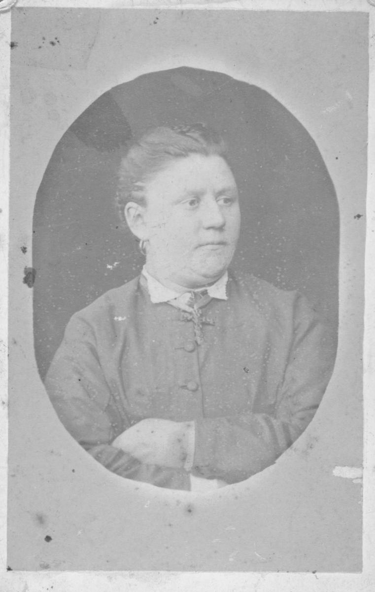 Portrett fra en eldre kvinne, (ikke identifisert). Hun er kledd i hvit bluse og draktjakke over, og hun bærer et stort kors i silkebånd rundt halsen. Bildet er tatt hos L. Schetnes' fotografiske atelier i Tromsø.