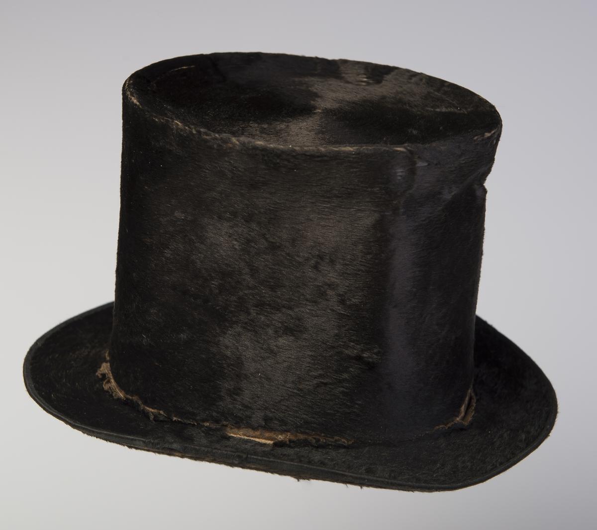 Flosshatt med høy stiv pull som er flat på toppen. Bremmen er flat fram og bak, noe  oppover bøyd på sidene. Bremmen er kantet med ripsbånd. Hatten er foret med mønstret papir. Trykk i pullen.