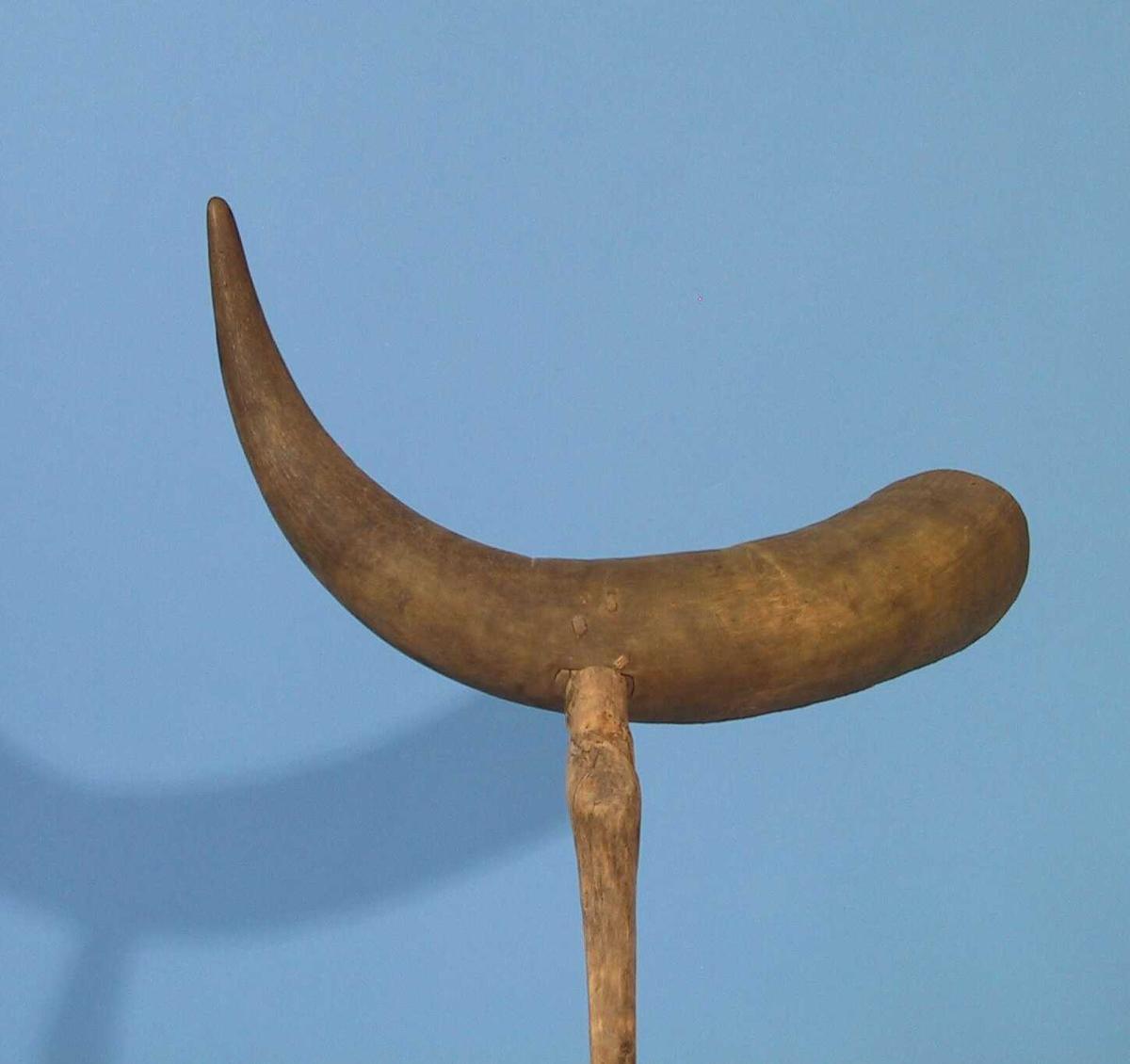 Vadhorn,  av kuhorn med skaft av einer.  Stort horn med dype innskjæringer etter snøret.  Korklukning med innskårne bokstaver   Å T.  Kneformet skaft.