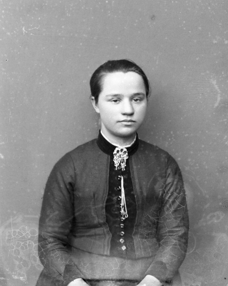 Ung kvinne i halvfigur, lerretbakgrunn