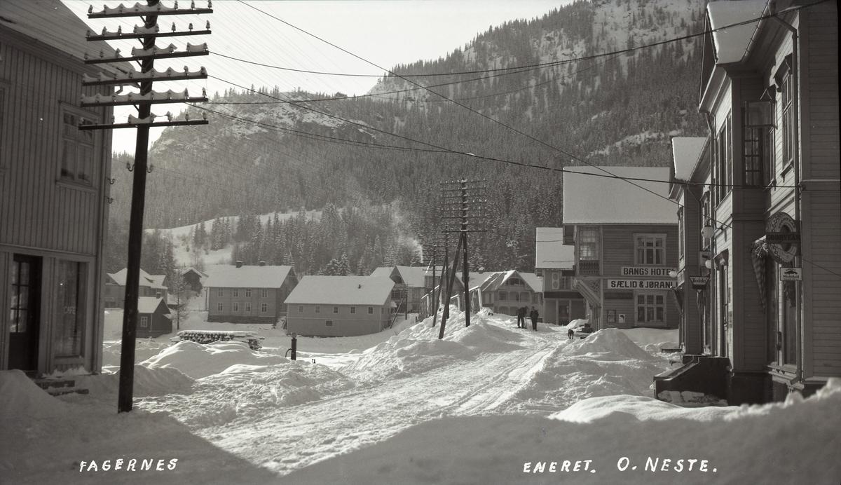 Butikker og hoteller langs snødekt gate på Fagernes, mot brua og Skarpsno