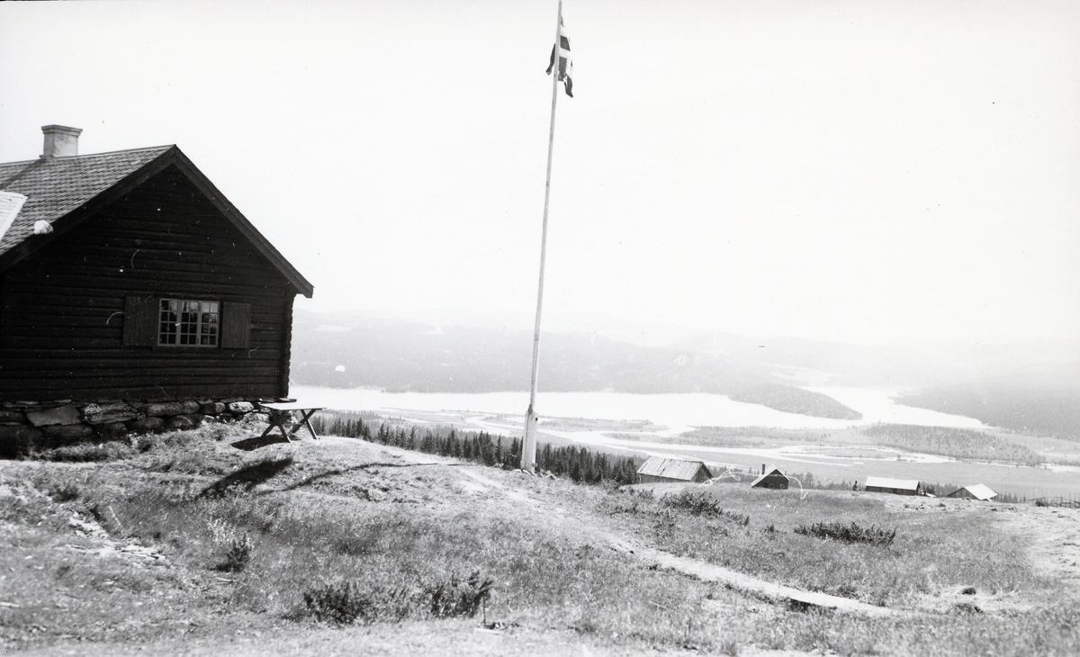 Tømmerhus ved flaggstang, med utsikt over stølslandskap og innsjø