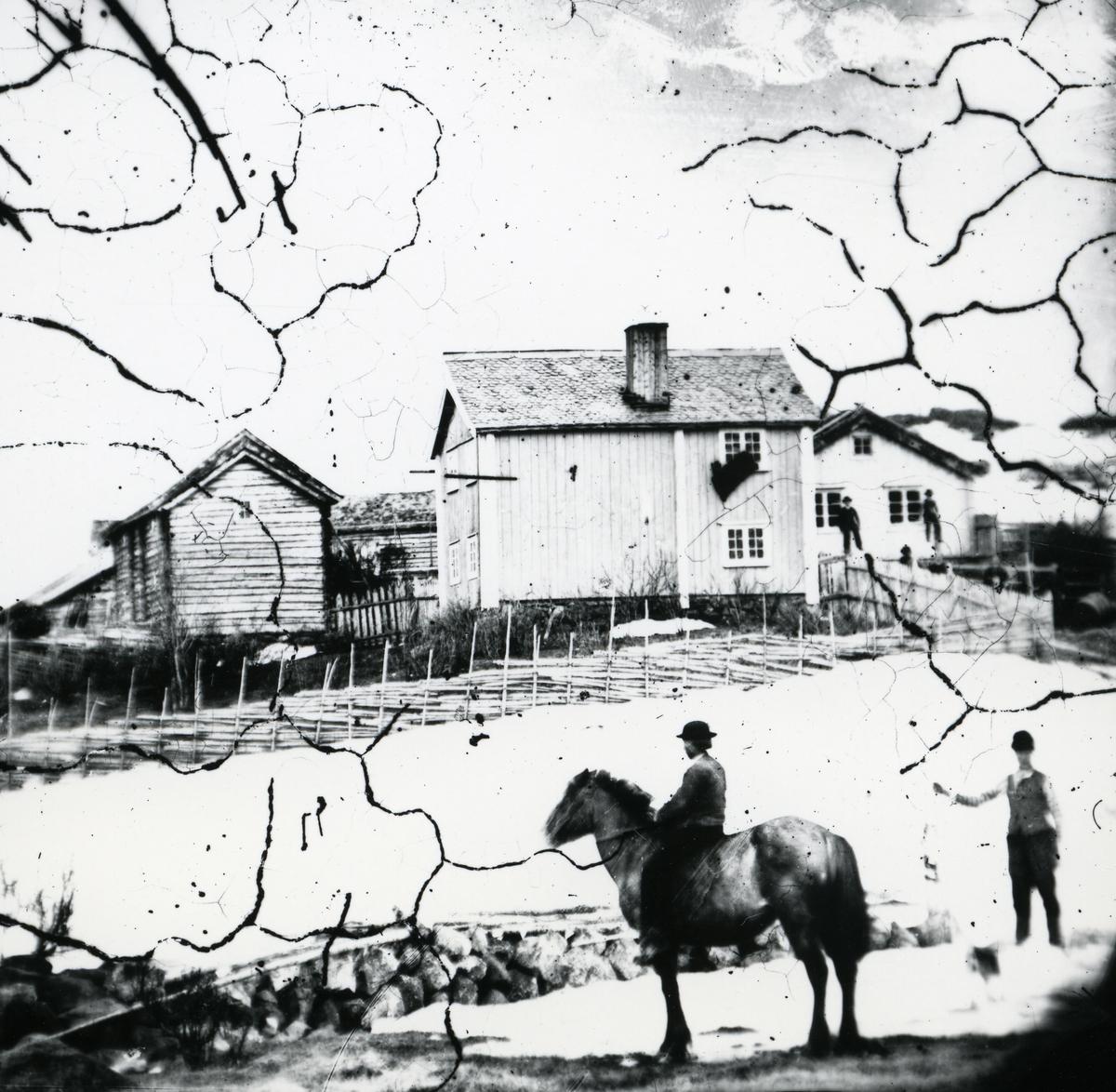Hus på gården Dal i Øylo, blant annet toetasjes panelkledd hovedbygning. To menn i framgrunnen, den ene på hest
