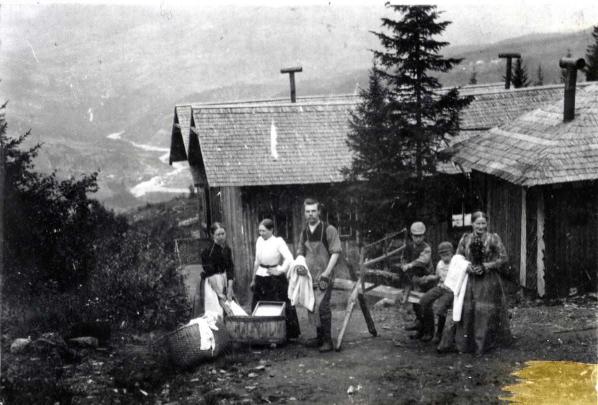Mennesker ved badehuset og vaskeriet på Breidablikk Sanatorium. Kvinner med vaskebalje og vaskebrett. Syver Framnes midt i bildet, og Kristine Hagene (Gimle) helt til høyre