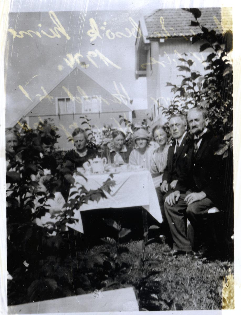 Mennesker rundt bord i hage
