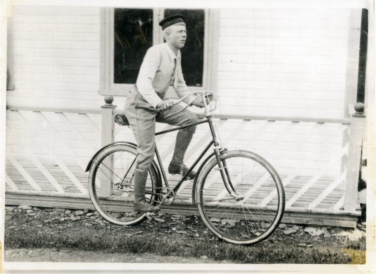 Ung mann på sykkel, fotografert framfor veranda