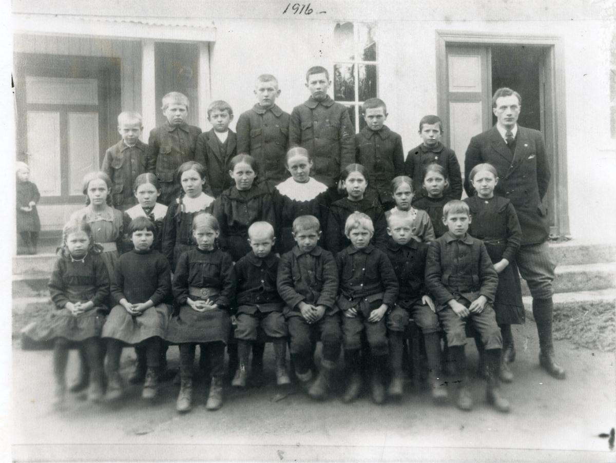 Gruppebilde av elever ved Strømmen skole i Begnadalen. Oppstilt utenfor skolebygningen. 1916
