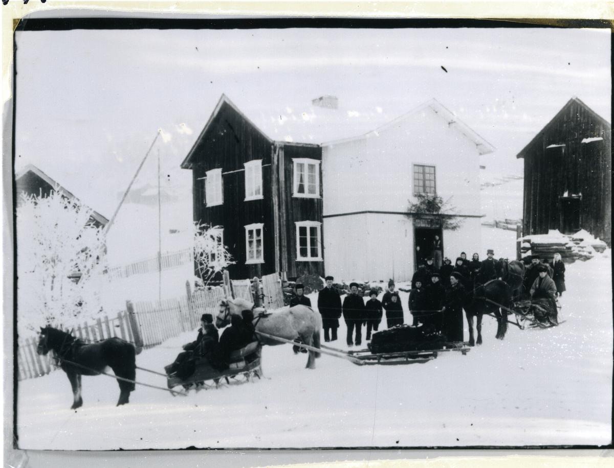 Gravferd i gamletunet på Sørre Røllång, Nord-Aurdal, mest sannsynlig etter 10-åringen Haldor Henriksson Ranum. Hester, sleder og mennesker utenfor gårdshus. Det er pyntet med granbar over inngangsdøra. Kiste på den ene sleden. Trær med rim på.