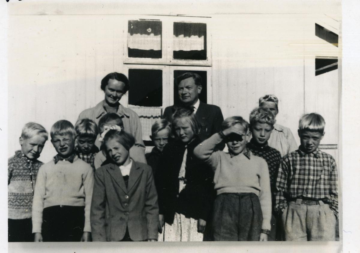 11 barn og to voksne oppstilt utenfor et hus. Er det en skoleklasse?