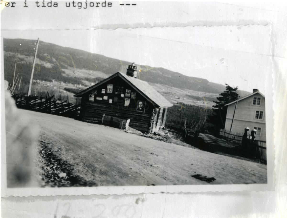 Bildet viser Torget i Volbu, Øystre Slidre. 1936. Plakatene på tømmerveggen er vedrørende stortingsvalget 19. oktober. Skigard.