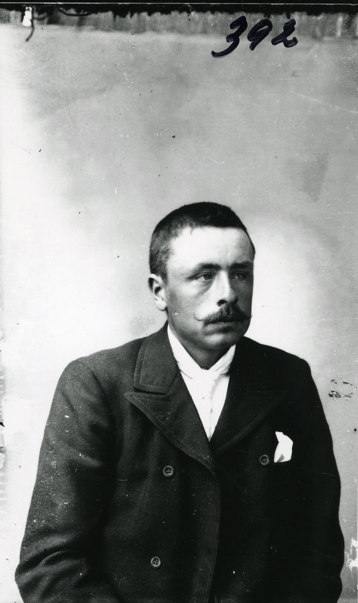 Portrett av mann i halvfigur. Dobbeltspent jakke, med hvitt lommetørkle i brystloma.