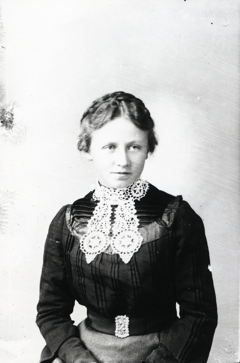 Ung kvinne avbildet i svart bluse og grått skjørt. Hvit, heklet krage og pyntet beltespenne.