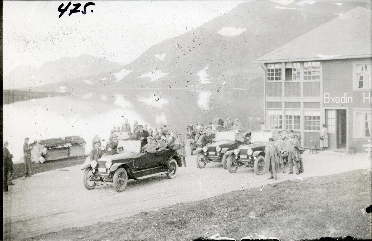 Biler og mennesker utenfor Bygdin Høyfjellshotell i 1930-åra. Innsjøen Bygdin midt i bildet.