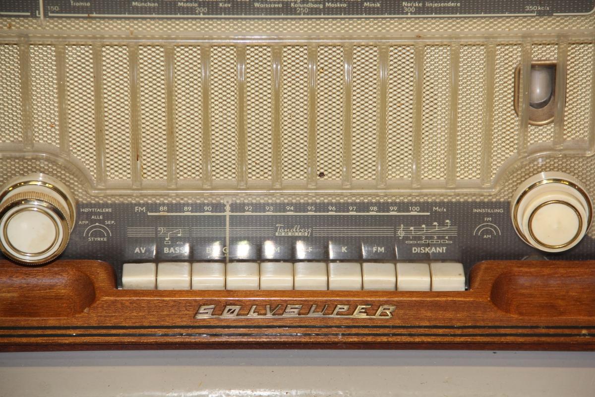 Form: Avrundet parallellogram, front m/frekvenser, tangenter og 2 betjeningsknapper, bakplate, ledningsuttak, kontakt