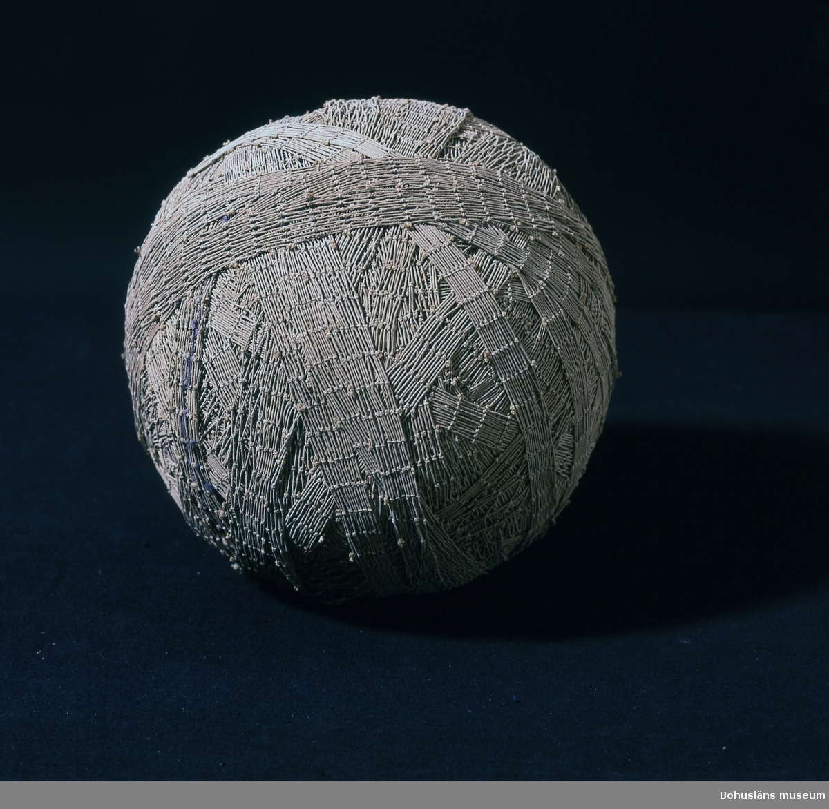 """Runt, grå-beige garnnystan bestående av kasserat fisknät. När gamla fisknät var uttjänta återanvändes de ofta till mattor. Att klippa mattrasor av garn var en sysselsättning för hela familjen - gamla, unga, kvinnor och män. Mattor med inslag av nät var starka och låg bra på golvet enligt givaren. Mattorna hade inslag av både nät och vanliga trasor. Det var viktigt att remsorna klipptes jämt. En del av nätet knöts fast i kökssoffan för att hålla det sträckt vilket gjorde det lättare att räkna stolpar och klippa efter dem och på så sätt få jämnbreda remsor. Nätet klipptes längs med den sida som inte var fäst i soffan och allt eftersom arbetet fortgick flyttades nätets fästpunkt. På en """"vad"""" var ca 15 - 20 stolpar en vanlig bredd. Vaden hade mindre maskor än nätet vilket innebar att det blev ett tätare inslag. """"Vad"""" var ofta färgat i blått eller grått och garnen ofta i olika bruna nyanser. Mattorna gjordes rent i saltvatten på så sätt blev de styva och låg plant på golvet och saltet förhindrade även färgerna att färga av sig.  Brukaren är givarens mor. Eventuellt kan nystanet vara tänkt att användas av givarens farmor som också bodde på Smögen. Tillverkaren är trolig. Han var givarens bror och mycket duktig på att klippa mattrasor av fisknät.  Maria Rödström, gift med Karl-Olof Rödström, f. 1916. Karl-Olof Rödström var son till Evert Rödström, f. 1898 och Irene Rödström (1903 - 1995). Evert och Irene är också föräldrar till Karin Rödström.  Evert är bror till Gertrud Linnea Gunnarsson, f. 1896 med dottern Berit Gunnarsson, f. 1922. Evert och Gertrud Linneas föräldrar är Frans Rödström, f. 1871 och Sofia Rödström , f. 1872  Se flera föremål från Smögen i samlingarna från denna Smögenfamilj. Intervju med Maria Rödström förvaras under Intervjuserien, Etnologi, Ämbetsarkivet."""