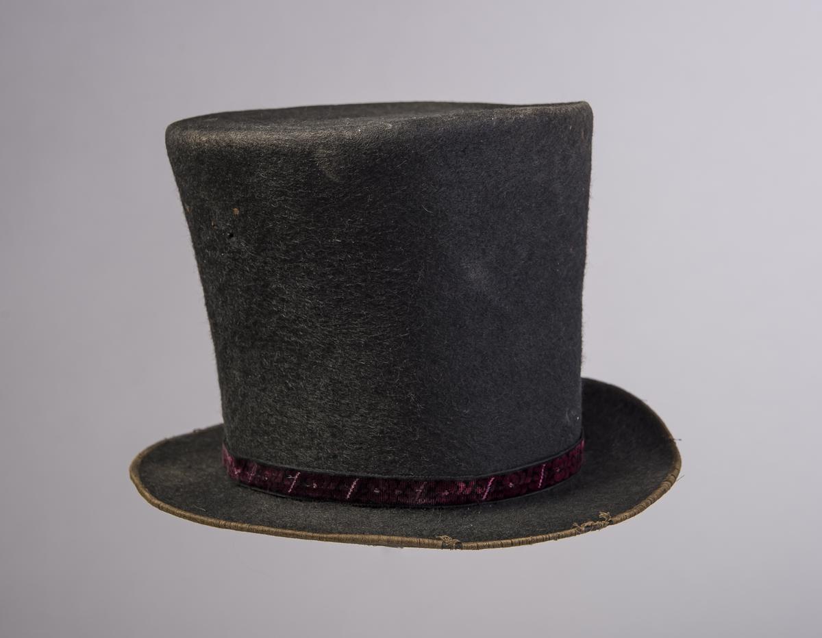 Filthatt med høy stiv pull som er flat på toppen. Rundt ytterkanten av bremmen er det påsydd et smalt bånd. Rundt nedre kant av pullen er det er smalt dekorbånd med liten spenne. Inne i pullen er det et papir med trykk og håndskrevet navn. Hatten har svettebånd og halve høyden av hatten er foret. Øvre del av hatten har større omkrets enn lenger nede. Denne type hatt er forløperen til flosshatt.