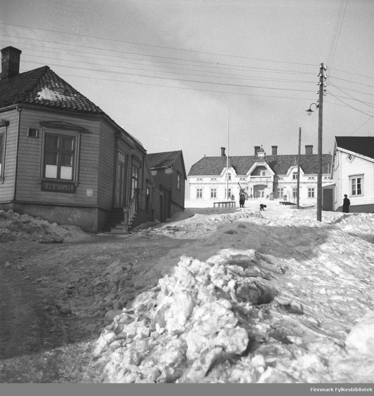 Foto fra Vadsø, avnTollbodgaten, også kalt Apotekerbakken. Til venstre sees Frelsesarmeens lokale, i enden sees Fylkesgården, også kalt Amtmannsgården. På høyre side i bildet står Moes hus. Bildet er muligens tatt i 1934. Fotograf ukjent.