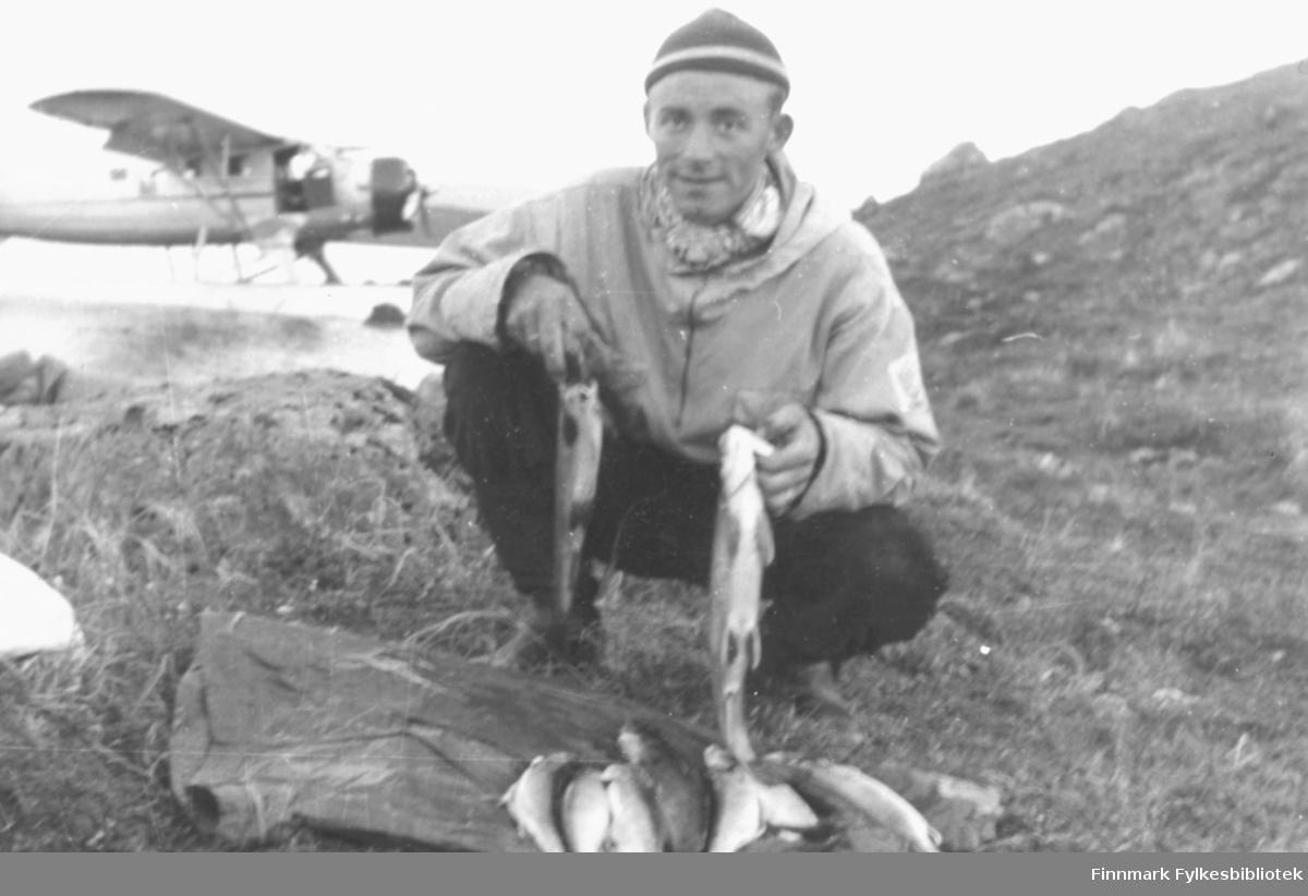 Dette bildet er tatt i løpet av helgen 12.-13. august 1955 og del av en serie bilder tatt på  fiskertur med sjøfly til det avsidesliggende Peskvannet. Her viser Ernst Lebesby fram noe av fangsten. Foto: Per Bjørgan.