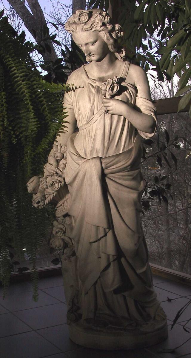 Stående   kvinne  med kjole som er drapert over hoftene  og knyttet foran, venstre skulder bar et  knapning over h. skulder og korte erme.  Hodet sterkt foroverbøyd,   blomsterkrans i håret og knute i nakken.  I høyre hånd holder hun er blomsterkurv:  hanken er brukket, i venstre hånd en liten bukett  som holdes opp mot brystet.