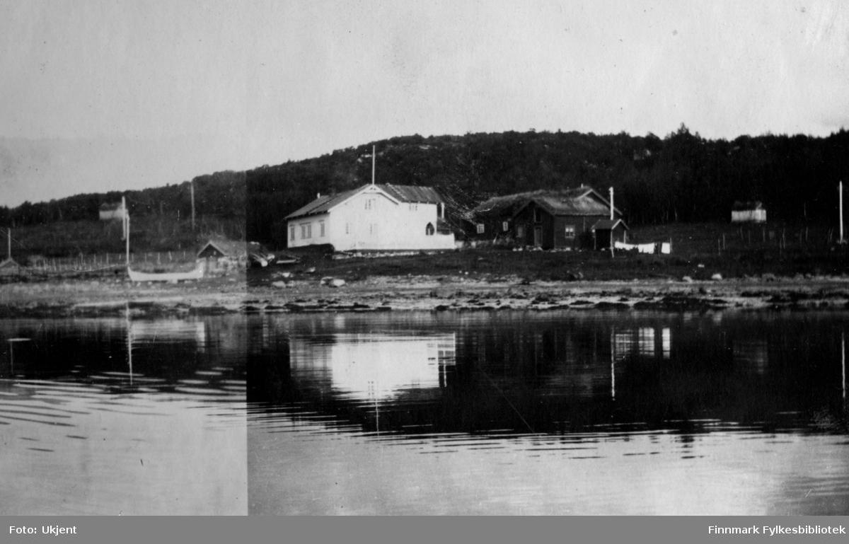 Gården Strømsnes i Jarfjord, bildet tatt fra sjøsiden. Bildet er muligens tatt i 1923. Husene på gården brente ned i 1947. På bildet kan man se fjæra og havet ved siden av bygningene og i bakgrunnen kan man se et lite fjell med skog på. Rundt om kring har det blitt satt opp gjerder og man kan se enkelte strømlinjer på området. Til venstre side av bildet kan ma se en båt på land.