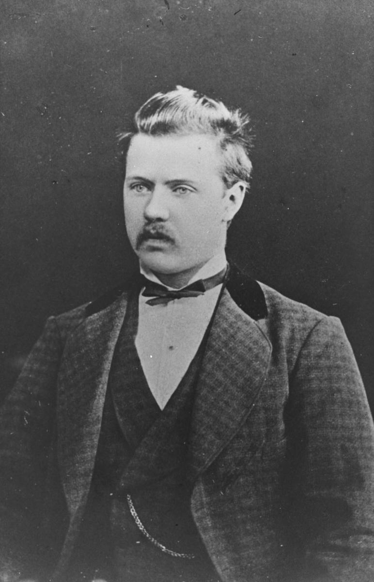 Halvkropsportrett av en mann, J.O.Monsen. Han er kled i en rutet dress