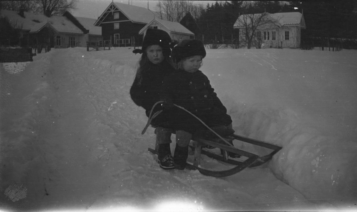 Fotoarkivet etter Gunnar Knudsen. Borgestad gård. To små jenter på en kjelke fotografert
