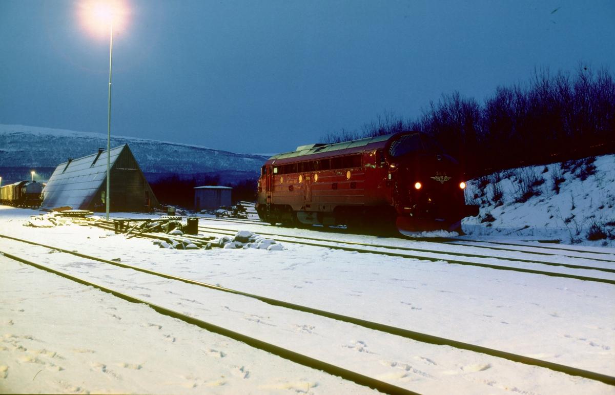 Kveld på Fauske stasjon. NSB dieselelektrisk lokomotiv Di 3 606 utenfor lokomotivstallen.