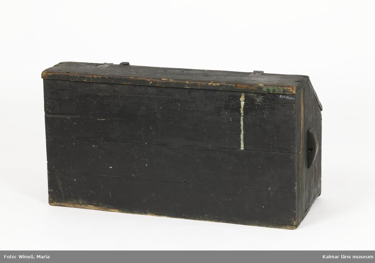 KLM 25128:4. Verkfat, trä, metall. Svartmålat verkfat av trä med rektangulär baksida och pulpetformad framsida. Locket består av tre bräder, två gångjärn och ett beslag av järn. Låset saknas. Framsida bestående av två bräder och gavlarna består av tre, respektive två bräder. Handtag tillverkade av träklossar med hål för rep. Endast ett av repen finns kvar. Baksidan består av fyra bräder. Inuti verkfatet låg fem stycken bitar tagel, utformade till sadelstoppning (KLM 25128:5:1-4).