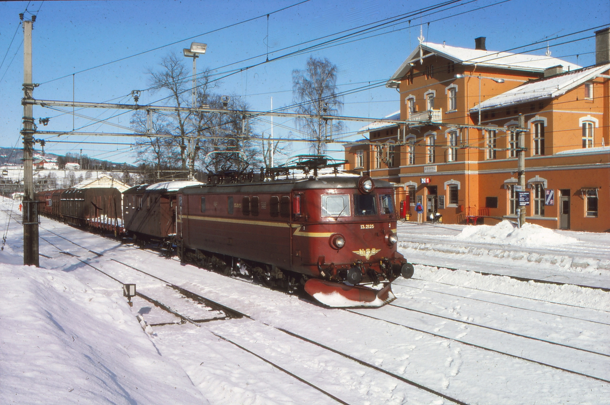 """NSB underveisgodstog 5072 Eidsvoll - Lillestrøm i Eidsvoll stasjon med elektrisk lokomotiv El 13 2125 og konduktørvogn. Godstoget var betjent med lokomotivfører, lokomotivførerassistent og overkonduktør (""""togfører""""), og skiftet på stasjonene underveis. Fotografen tjenestegjorde som lokf.ass. i toget."""