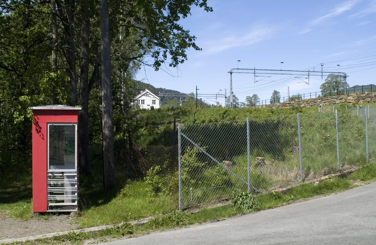 Denne telefonkiosken står ved Sira jernbanestasjon, og er en av de 100 vernede telefonkioskene i Norge. De røde telefonkioskene ble laget av hovedverkstedet til Telenor (Telegrafverket, Televerket).  Målene er så å si uforandret.  Vi har dessverre ikke hatt kapasitet til å gjøre grundige mål av hver enkelt kiosk som er vernet.  Blant annet er vekten og høyden på døra endret fra tegningene til hovedverkstedet fra 1933. Målene fra 1933 var: Høyde 2500 mm + sokkel på ca 70 mm Grunnflate 1000x1000 mm. Vekt 850 kg. Mange av oss har minner knyttet til den lille røde bygningen. Historien om telefonkiosken er på mange måter historien om oss.  Derfor ble 100 av de røde telefonkioskene rundt om i landet vernet i 1997. Dette er en av dem.