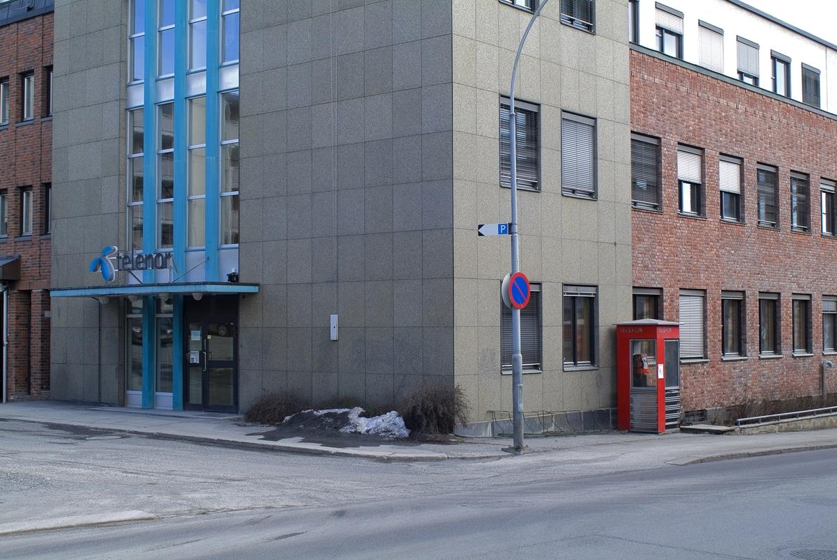 Denne telefonkiosken står i Kirkegata 45, Lillehammer, og er en av de 100 vernede telefonkioskene i Norge. De røde telefonkioskene ble laget av hovedverkstedet til Telenor (Telegrafverket, Televerket). Målene er så å si uforandret.  Vi har dessverre ikke hatt kapasitet til å gjøre grundige mål av hver enkelt kiosk som er vernet.  Blant annet er vekten og høyden på døra endret fra tegningene til hovedverkstedet fra 1933. Målene fra 1933 var: Høyde 2500 mm + sokkel på ca 70 mm Grunnflate 1000x1000 mm. Vekt 850 kg. Mange av oss har minner knyttet til den lille røde bygningen. Historien om telefonkiosken er på mange måter historien om oss.  Derfor ble 100 av de røde telefonkioskene rundt om i landet vernet i 1997. Dette er en av dem.