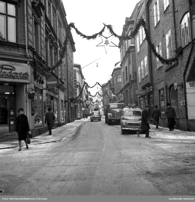 Nybrogatan i Sundsvall med bland annat frukthandlare Berg och olika butiker och hotell utmed gatan. Fotograferat för Nybrogatans Allehanda.