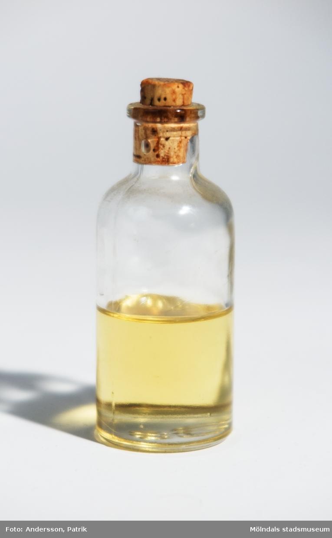 """Flaska med Ricinolja. Oljan är svagt gulaktig, klar och genomskinande. Den brukar sakna doft. Smaken ska vara fet och mild.Flaskan är av glas och korken är av materialet kork. På flaskan finns en påklistrad vit pappersetikett, där det står: """"APOTEKET I MÖLNDAL   Ricinolja"""", tryckt med svarta bokstäver.I botten av flaskan finns """"L   50"""" gjutet i glaset.Ricinolja är en fet trögflytande olja som pressas ur fröna från växten Ricinus communis. Oljan är en naturlig produkt som används till skönhetsvård och smörjolja till bland annat motorer. Förr användes den även som laxermedel, vilket inte är så vanligt i Sverige längre. Men säljs dock fortfarande på Apoteket. I andra länder är Ricinoljan fortfarande ett vanligt laxermedel. Oljan kan göra håret glansigare och sedan länge har den använts för att lägga håret.En nackdel är att oljan kletar ner omgivningen till exempel vid smörjning och kräver därför stor rengöring efter användning.MåttHöjd utan kork: 92 mm, Höjd med kork: 99 mm, Diam: 37 mm"""