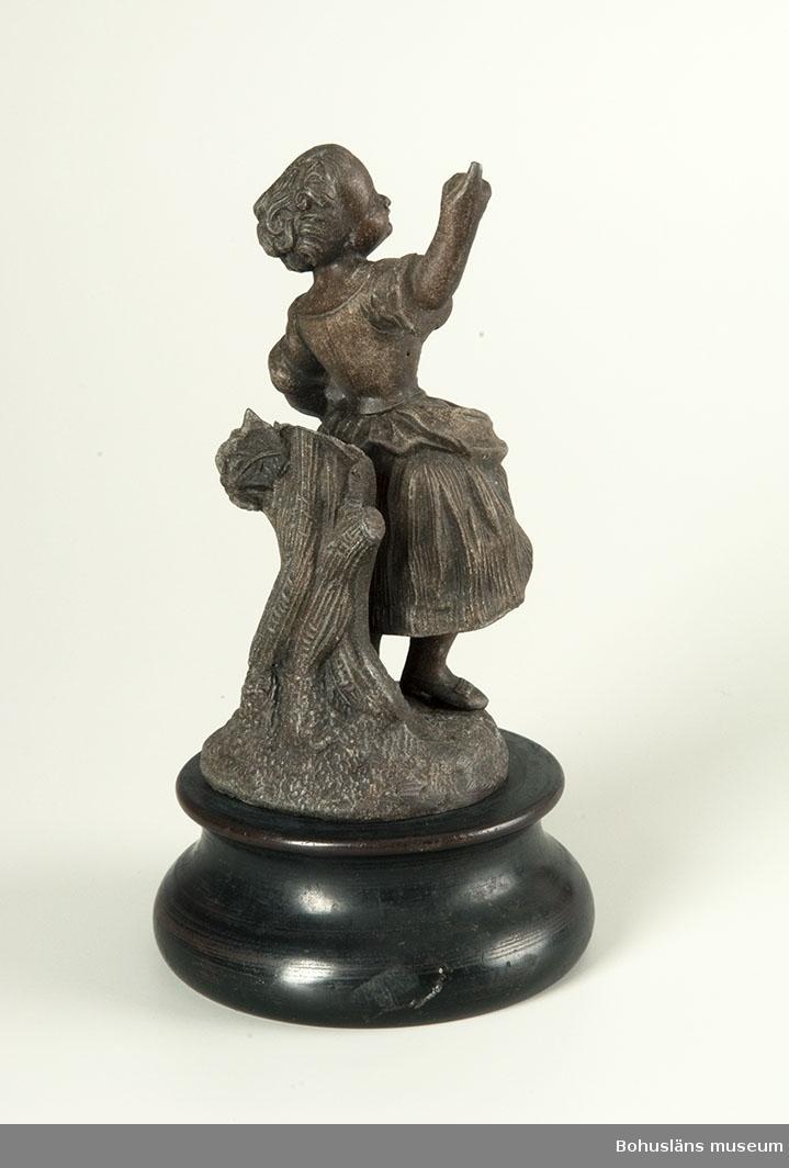 """Figuren är gjuten av en mörkt grå metall som behandlats/patinerats med en brun färg. Om det inte hade varit p.g.a. nötningsskador så hade man kunnat tro att figuren var av brons. Statyetten visar en flicka i nyrokokoklänning med ihopsamlat förkläde som står lutad mot en avsågad trädstam. Figuren är skruvad fast i sockel av svarvat, mörkbetsat trä. Frankrike troligt tillverkningsland; 1800-talets andra hälft. P.g.a. skador i ytskiktet nederst på metallsockeln kan man fundera på om området använts för att tända tändstickor på jämför funktionen för UM002602.  Ur """"Gåfvor till Uddevalla museum"""": 1 pendang till ställ för svaveltändstickor (statyett) [se UM002602]  Ur handskrivna katalogen 1957-1958: Flickstatyett av brons H. 17,5. Statyett på bas av trä. Basen och statyetten skilda. Eljest hel.  Lappkatalog: K7"""