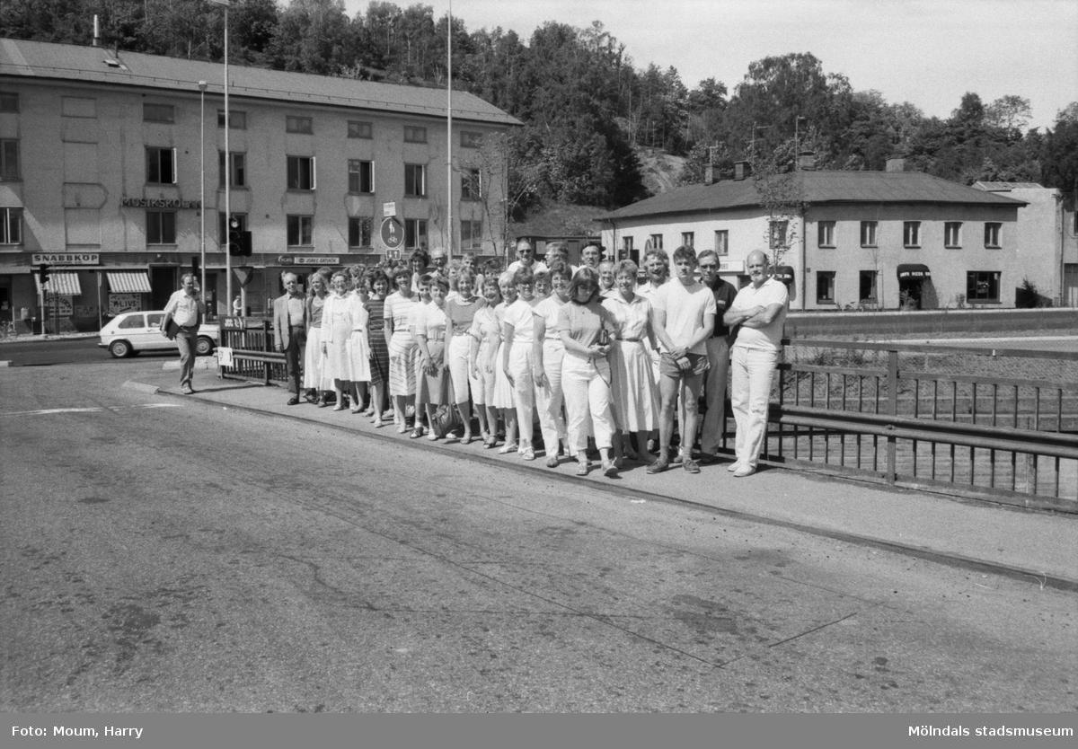 """Mölndals Körsällskap fotograferade på Forsebron i Mölndal, år 1985. """"Mölndals Körsällskap åker på turné till Ungern.""""  För mer information om bilden se under tilläggsinformation."""