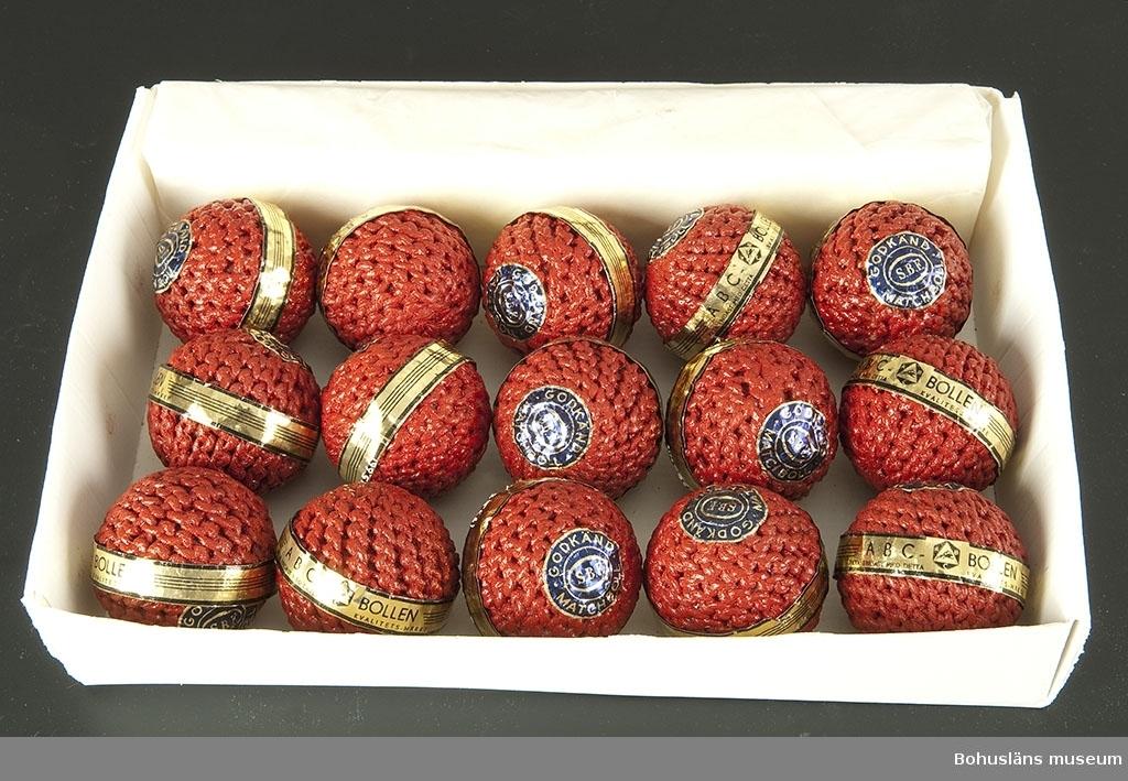 """Rödmålade bandybollar med originaletikett. Samtliga bollar fabriksnya och oanvända. De är försedda med pappersremsa i svart och guldfärg med texten: """"ABC-BOLLEN. Äkta endast med detta kvalitetsmärke"""" och ABC-fabrikernas logotyp samt en cirkelrund lapp i blått med guldtext: """"Godkänd matchboll SBF"""". SBF= Svenska Bandyförbundet.  Tillverkningen skedde delvis som hemarbete. Runt en limmad korkkärna syddes med snören en fast rund form. Dessa """"halvfabrikat"""" hämtades in till fabriken av springpojkar som cyklade runt på paketcyklar. Bollarna doppades därefter i röda färgbad. En del bandybollar doppades också i lack så att de skulle bli riktigt hårda.  Bandyn har i Västsverige varit dominerande bland vinterislagspelen under stora delar av 1900-talet.  Första katalogen med företagets produkter kom år 1911. Där fanns seldon, fotbollar, benskydd och slungbollar presenterade. Redan i 1915 års katalog dyker bandyklubbor och bandybollar upp.  ABC-fabrikerna (Aktiebolaget Bröderna Claesson) hade en omfattande tillverkning av sport- och fritidsartiklar. Under en tid var de Nordeuropas största tillverkare.  Bollarna är inköpta på Lions Loppmarknad i Vänersborg hösten 1995."""