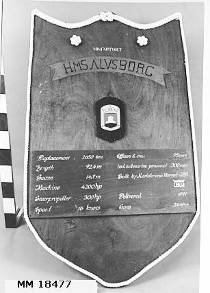 """Informationstavla i form av vapensköld av fernissad mahogny. I mitten överst banderoll av mässingsplåt med punsad text övermålad i svart: """"HMS ÄLVSBORG"""" samt ovanför """"MINFARTYGET"""" i vitt. Nederst rektangulär platta med uppgifter skrivna med vit text: """"Deplacement 2650ton  Lenght 92,4m  Beam 14,7m  Machine 4200hp    Steerpropeller 300hp  Speed 16knots  Officers&crew 95men  incl submarine personnel 300men  bulit by Karlskrona Varvet AB  Delivered 1971  Guns 3x40mm"""". Baksidan är försedd med hopfällbart stativ av trä, att användas för placering på kajen, samt byglar för upphängning."""