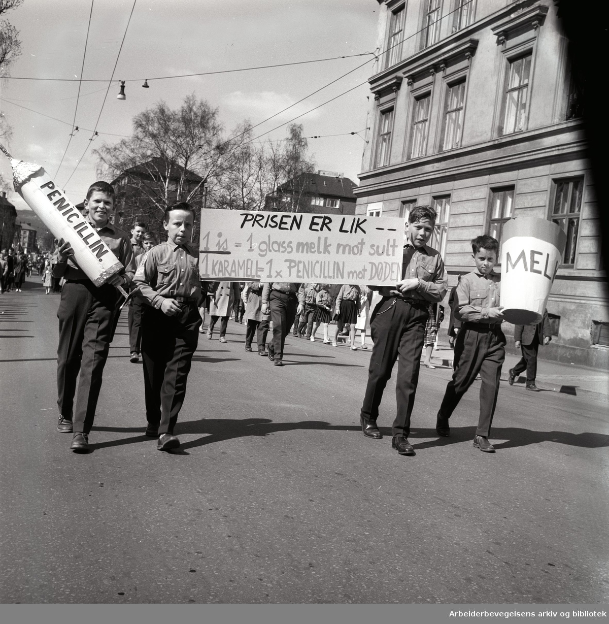 1. mai 1960 i Oslo. Parole: Prisen er lik 1 is = 1 glass melk mot sult. 1 karamell = 1 x penicilin mot døden.