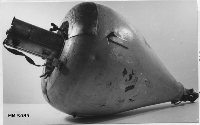 """Bojtelefon, har tillhört ubåten U 3.  (äldre). Ej komplett. Av järn, päronformad. I centrum av bojen ett cylindriskt urtag för dosan till handmikrotelefonen. Bojen är gulmålad med en vit ring på översidan. På bojens översida två metallplåtar med instruktioner med följande text: """"Bojtelefon med telefonkabel till undervattensbåten No 3 som här sjunkit. Iakttag varsamhet så att bojrep eller kabel ej utsättes för påfrestning. Underrätta myndigheterna. 1. Avlyft locket. Sedan muttrarna lossats (om behövligt med vidfästade nyckel). 2. Lyft upp dosan. 3. Följ föreskrifterna å dosan."""". Kabel och lock saknas till bojen."""