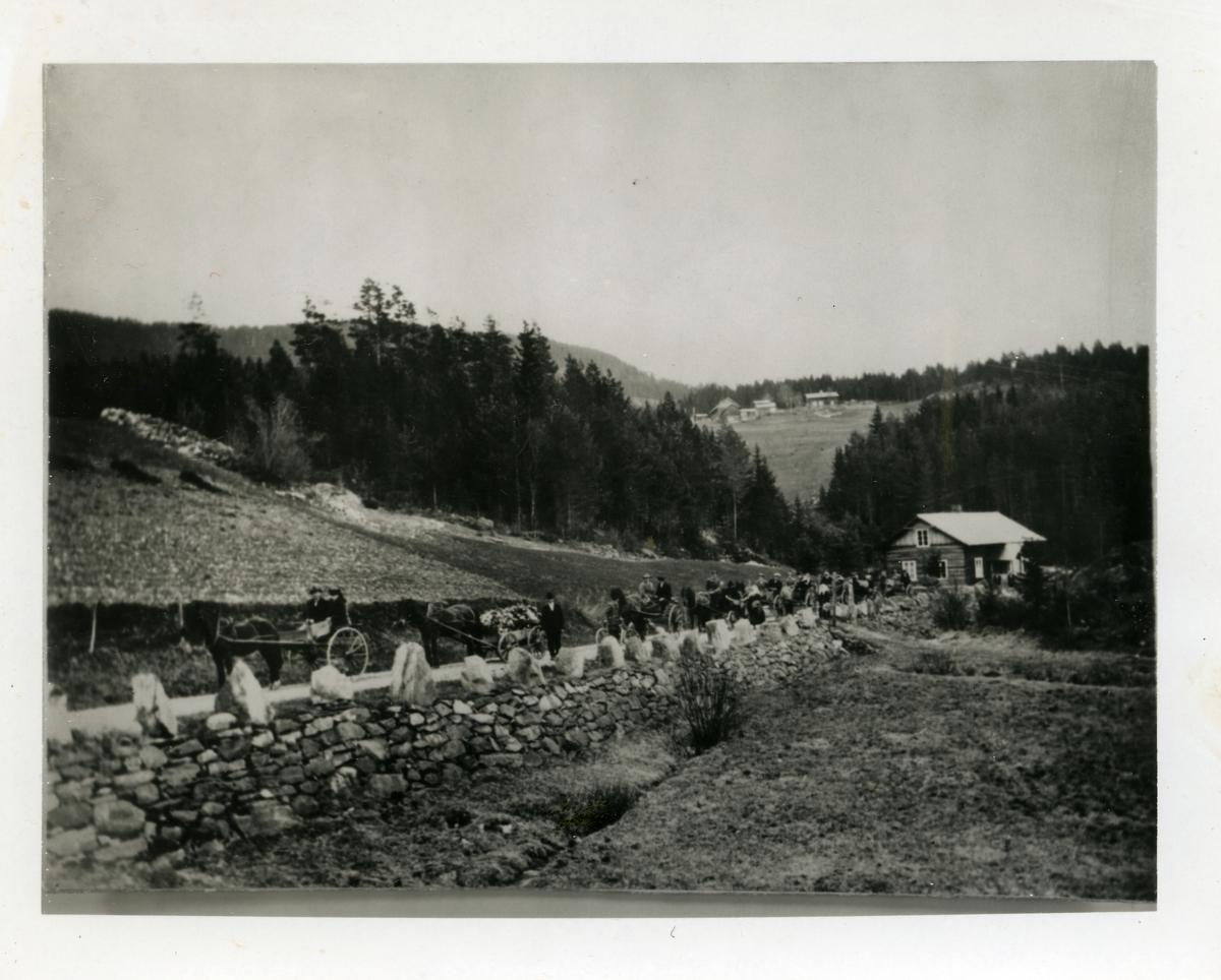 Gravferdsfølge etter Knut Syversen Knutslien (15.11.1847-12.05.1926). I første karjol sitter prost Dypsjord og kona hans, deretter følger Syver Knutslien med kista til faren. I bakgrunnen sees Sørskogen bedehus og garden Søre Knutslien.