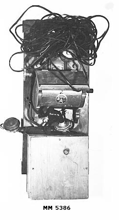 Telefon, större väggapparat. Fastsatt på plint av trä. Handtaget till hör- och taltratten är trasigt.