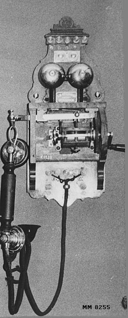 """Väggtelefon av mindre modell troligen från slutet av 1800-talet eller början av 1900-talet. Innesluten i en kåpa av mahogny. Kåpan trasig. Märkt: """"L.M. Ericsson & Co Patent Stockholm""""."""
