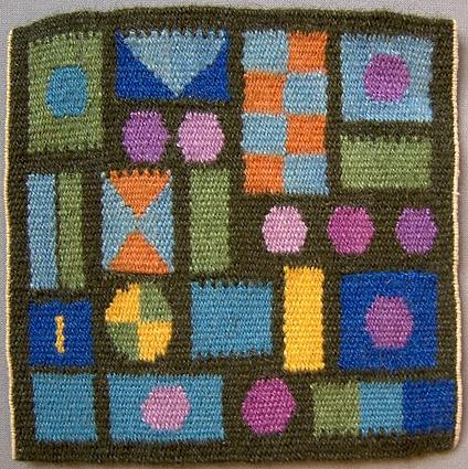 Vävprov, flamskväv. Kvadrat med mönster i form av rutor, rektanglar och rundlar i blått, lila, grönt, gult och orange på mörkgrön botten. Varp i halvblekt/vitt lingarn. Inslag i kulört ullgarn. Troligen komponerad av Anna Hådell. 1960-tal.